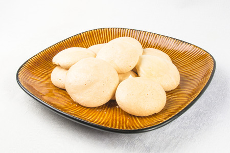 brown plate with meringues on a white background Stock Photo