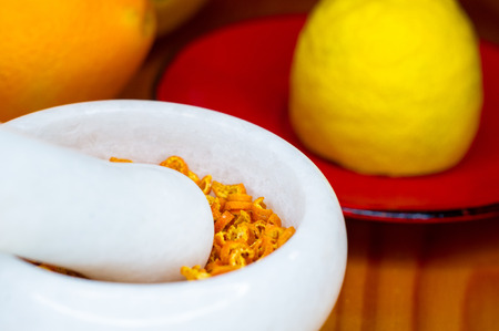 White marble mortar and pestle with the dried orange zest Stock Photo