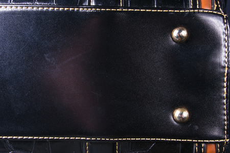 closeup of buckles, clasps, zippers, pockets, fasteners, fittings and seams on black leather hand bag