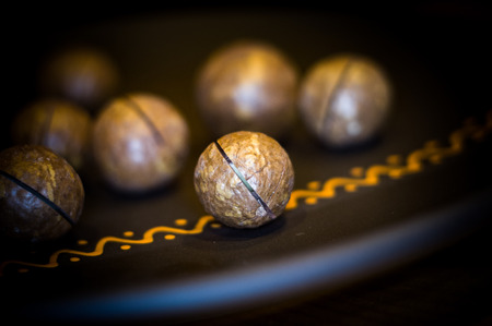 macadamia, Australian nut in a ceramic plate on a wooden table, close-up
