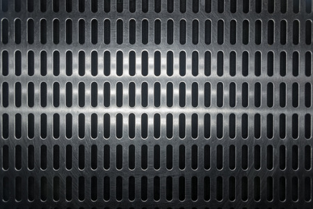 stainless steel grating with oblong holes on black background, close-up 版權商用圖片