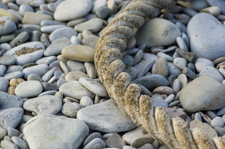 old worn battered marine rope on the pebble beach on a Sunny summer day, top view