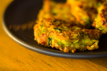 Fried vegetable fritters with zucchini, carrots, herbs, eggs, seasonings and cheese, close-up, selective focus