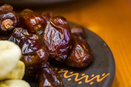 dried dates and figs in a ceramic plate on a wooden table, close-up Stock Photo