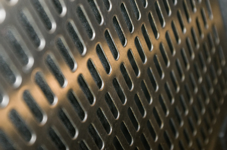 stainless steel grating with oblong holes on black background, close-up Banco de Imagens