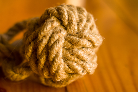 fender - marine knot of thick brown rope on a wooden background, closeup Stock Photo