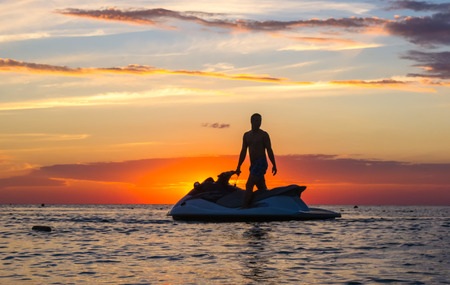 silhouette of a man on a jet ski in the sun on the sea sunset in summer evening Banque d'images
