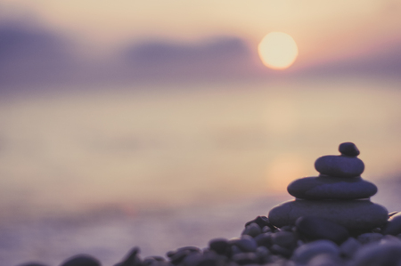 folded pyramid Zen pebble stones on the sea beach at sunset