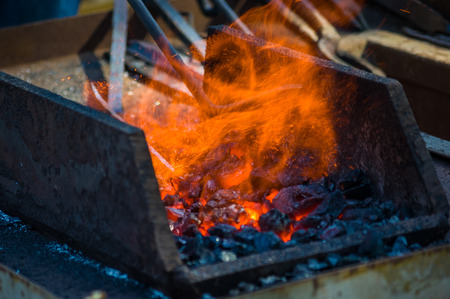 blacksmith furnace with burning coals, tools, and glowing hot metal workpieces, close-up 免版税图像