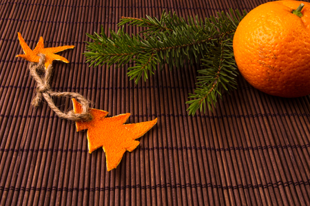 New Year Concept. Christmas decorations hand made from tangerine peel, fir-tree branches and the fruits of mandarin orange on bamboo mat background Stockfoto - 116145885