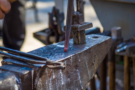 blacksmith performs the forging of hot glowing horseshoe on the anvil, close-up Imagens