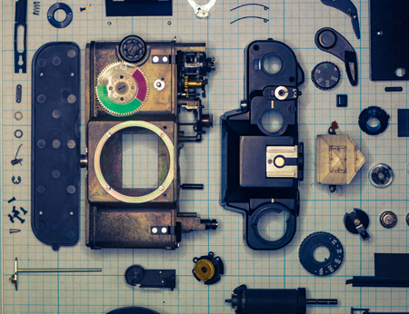 parts are completely disassembled old retro film SLR camera on graph paper, close-up, toned