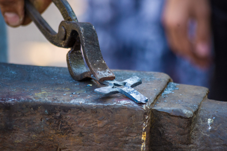 blacksmith performs the forging of hot glowing metal on the anvil, close-up 免版税图像
