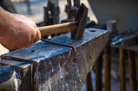 blacksmith performs the forging of hot glowing metal on the anvil, close-up Imagens