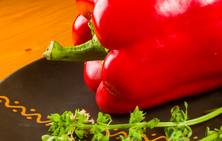 a freshest red paprika, bell pepper in ceramic plate with basil flowers on wooden background, close up