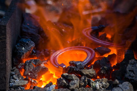 blacksmith furnace with burning coals, tools, and glowing hot horseshoe, close-up