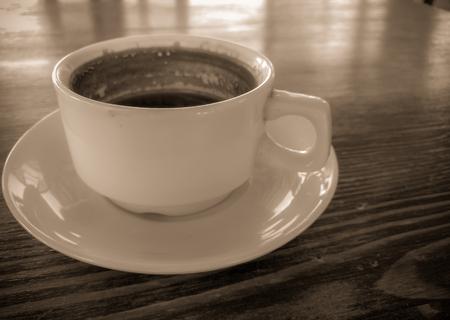 eine Tasse natürlichen schwarzen Kaffee auf einem Holztisch in einem Café am Meer, Nahaufnahme close Standard-Bild
