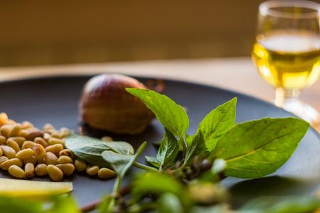 Frische Zutaten für die Zubereitung italienischer Pesto-Sauce - Zitronen-Basilikum-Zweige, geschälte Samen von Zedernnüssen, große Knoblauchzehe, griechisches Olivenöl, Parmesan, auf einer Keramikplatte, in verstreutem Sonnenlicht Standard-Bild