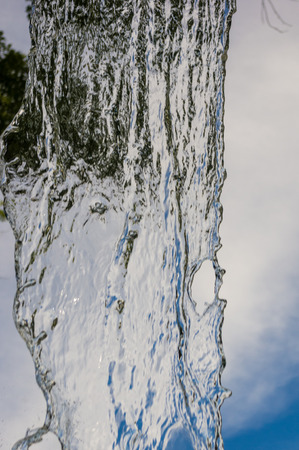 transparent falling water vertical flows against a blue sky and green landscape, close-up Banco de Imagens - 120943063