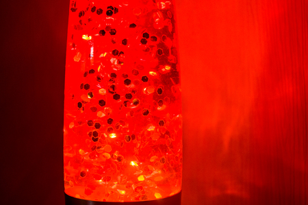 Orange lava lamp with bright stars at night on a red background, close up