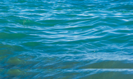 Die Seelandschaft ist ein Kieselstrand mit Wellen aus weißem Schaum, einem wunderschönen Himmel mit Wolken und einem warmen Sommertag