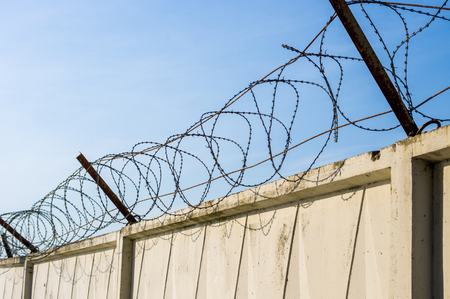 Concrete wall with razor barbed tape wire on blue sky background