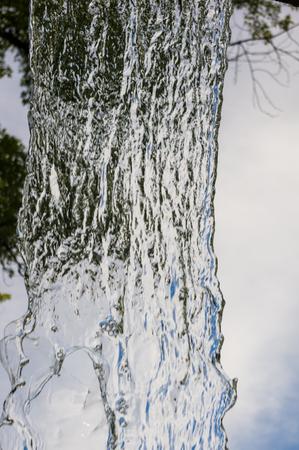 transparent falling water vertical flows against a blue sky and green landscape, close-up Banco de Imagens - 121261663