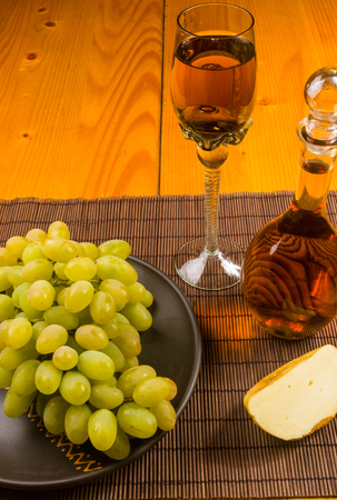 still life - a large brush of green grapes in a ceramic plate, a decanter and a glass of wine and cheese on a bamboo mat Banque d'images - 122795049