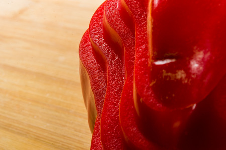 stacked pile of sliced fresh red paprika, bell pepper on bamboo cutting Board, close up Фото со стока