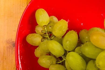 still life - a large brush of green grapes with water drops in a red ceramic plate on a wooden background Banque d'images - 122795120