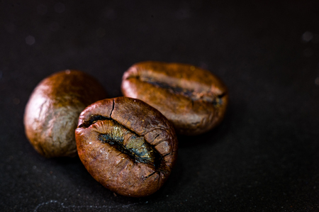 Brown roasted coffee beans on black background, close-up, macro Foto de archivo - 122795156