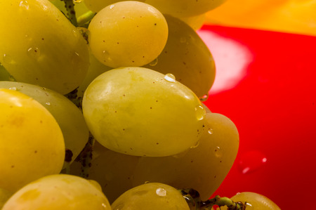 still life - a large brush of green grapes with water drops in a red ceramic plate on a wooden background Banque d'images - 122795419