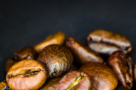 Brown roasted coffee beans on black background, close-up, macro Foto de archivo - 122795430
