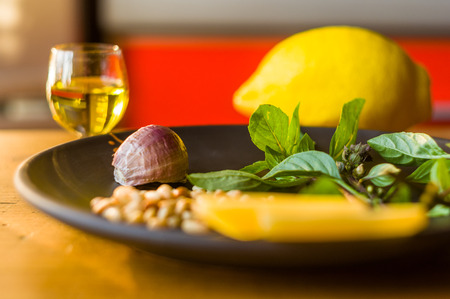 Fresh ingredients for preparing Italian pesto sauce - lemon basil sprigs, peeled seeds of cedar nuts, large garlic clove, Greek olive oil, Parmesan cheese, on a ceramic plate, in scattered sunlight