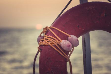 Orange emergency lifebuoy on a pebbly sea beach Reklamní fotografie