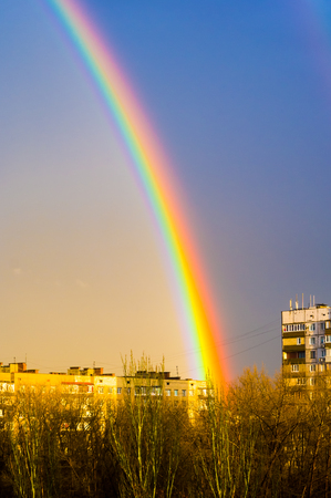 Natural double rainbow over green trees, city landscape