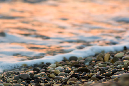 pebble stones on the sea beach on a warm summer evening at sunset, the rolling waves of the blue sea with white foam