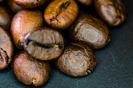 Brown roasted coffee beans on black background, close-up, macro Stok Fotoğraf
