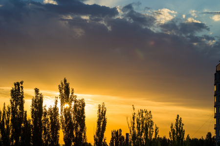 Landscape with dramatic light - beautiful golden sunset with saturated sky and clouds, peaceful nature serene background.