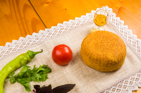 still life - national Adyghe cheese homemade on a woven cloth, with Basil, tomato, sesame oil, chili pepper, on a wooden table, close-up