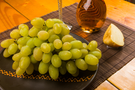 still life - a large brush of green grapes in a ceramic plate, a decanter and a glass of wine and cheese on a bamboo mat Stok Fotoğraf