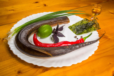 still life - smoked garfish with lime, Basil, green onions, chili, nori chips, spices, olive oil in a white ceramic dish, on a wooden table Stok Fotoğraf
