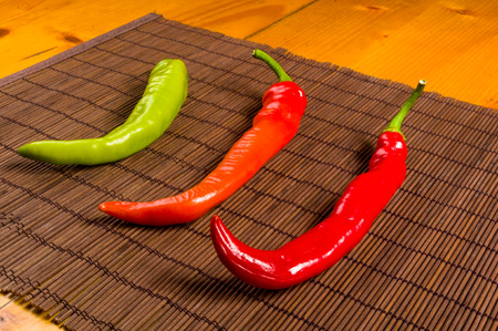 a colorful mix of the freshest and hottest chili peppers on a bamboo mat, close up Stok Fotoğraf