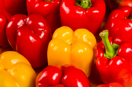 a colorful mix of the freshest red and yellow paprika, bell pepper on wooden background, close up