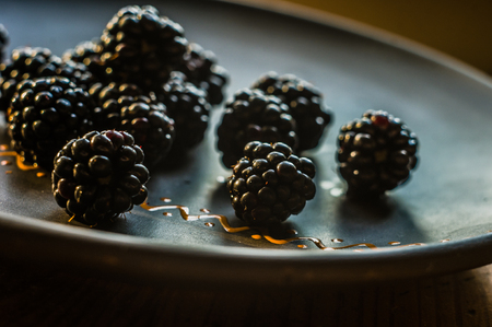 large juicy fresh blackberry berries on a ceramic plate, close-up