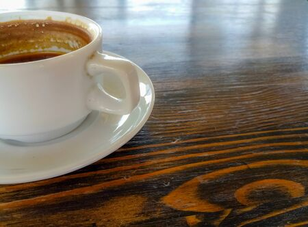 a Cup of natural black coffee on a wooden table in a seaside cafe, close-up