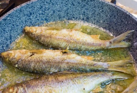 fried river fish with crispy crust in a frying pan, homemade dish Stok Fotoğraf