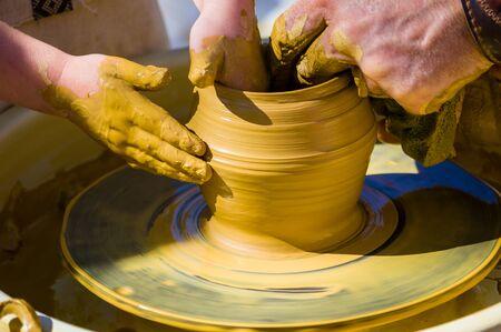 Mains du maître Potter et les mains des enfants, formation de l'enfant à la production de poterie sur un tour de potier, gros plan