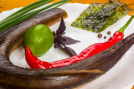 still life - smoked garfish with lime, Basil, green onions, chili, nori chips, spices, olive oil in a white ceramic dish, on a wooden table 스톡 콘텐츠