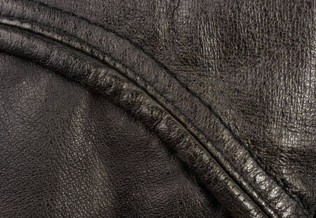 Old vintage genuine soft black leather texture background, top layer with pores and scratches, macro Фото со стока